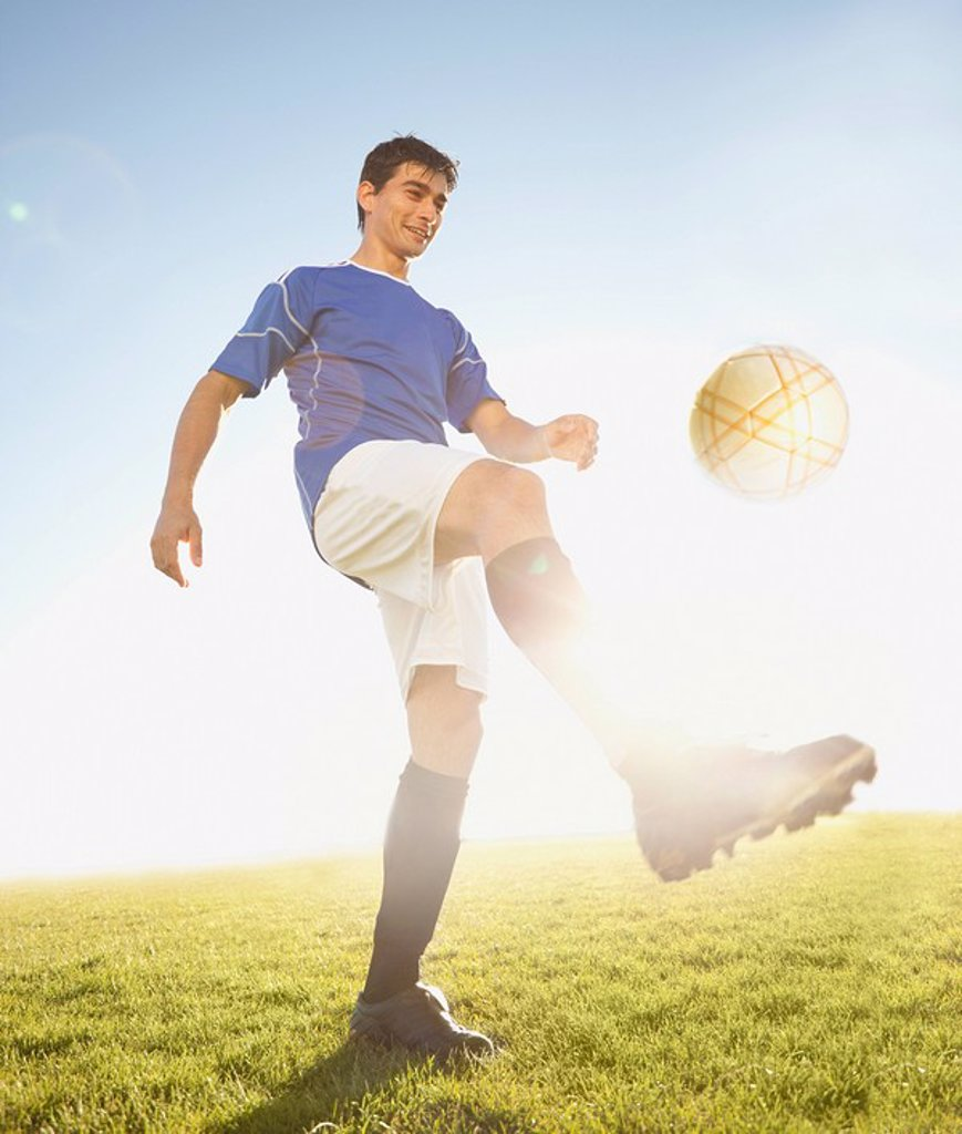 Soccer player kicking the ball : Stock Photo