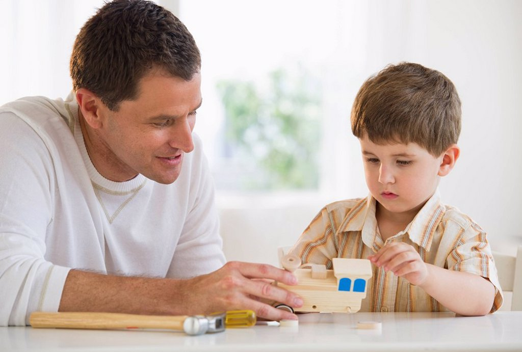 Father and son building a wooden train : Stock Photo