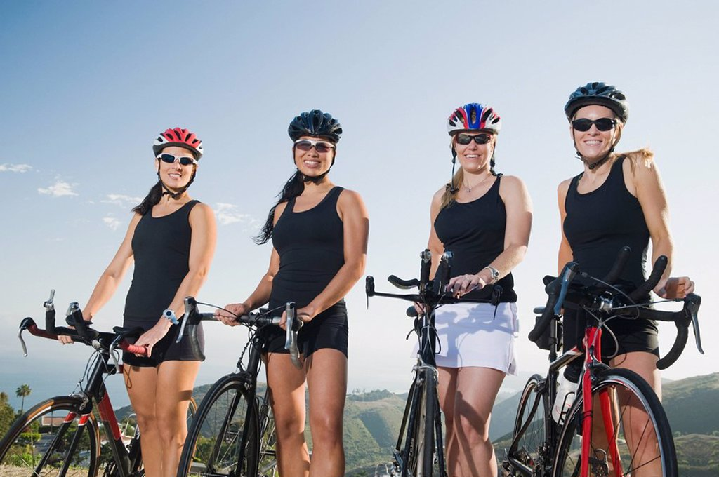 Cyclists standing beside their bikes on the side of the road : Stock Photo