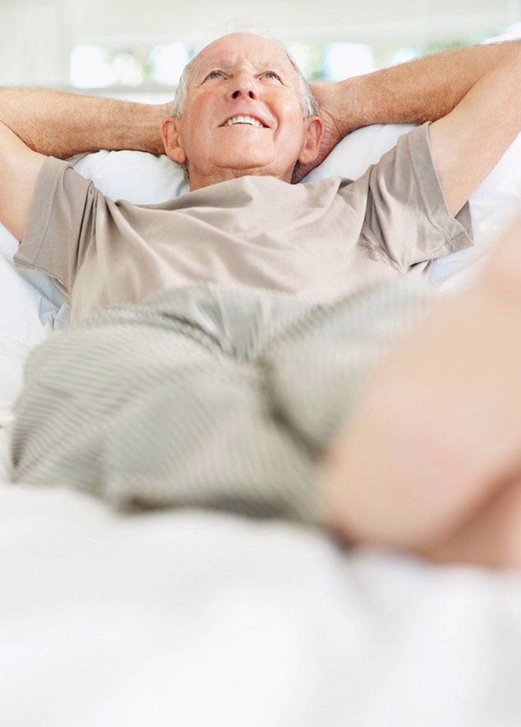 Relaxed senior man lying on bed : Stock Photo