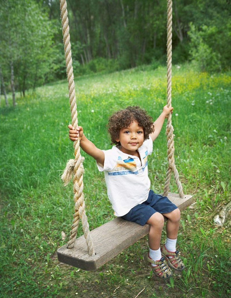 Young child sitting on large outdoor swing : Stock Photo