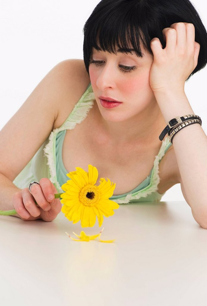 Stock Photo: 1795R-32722 Sad woman holding a flower