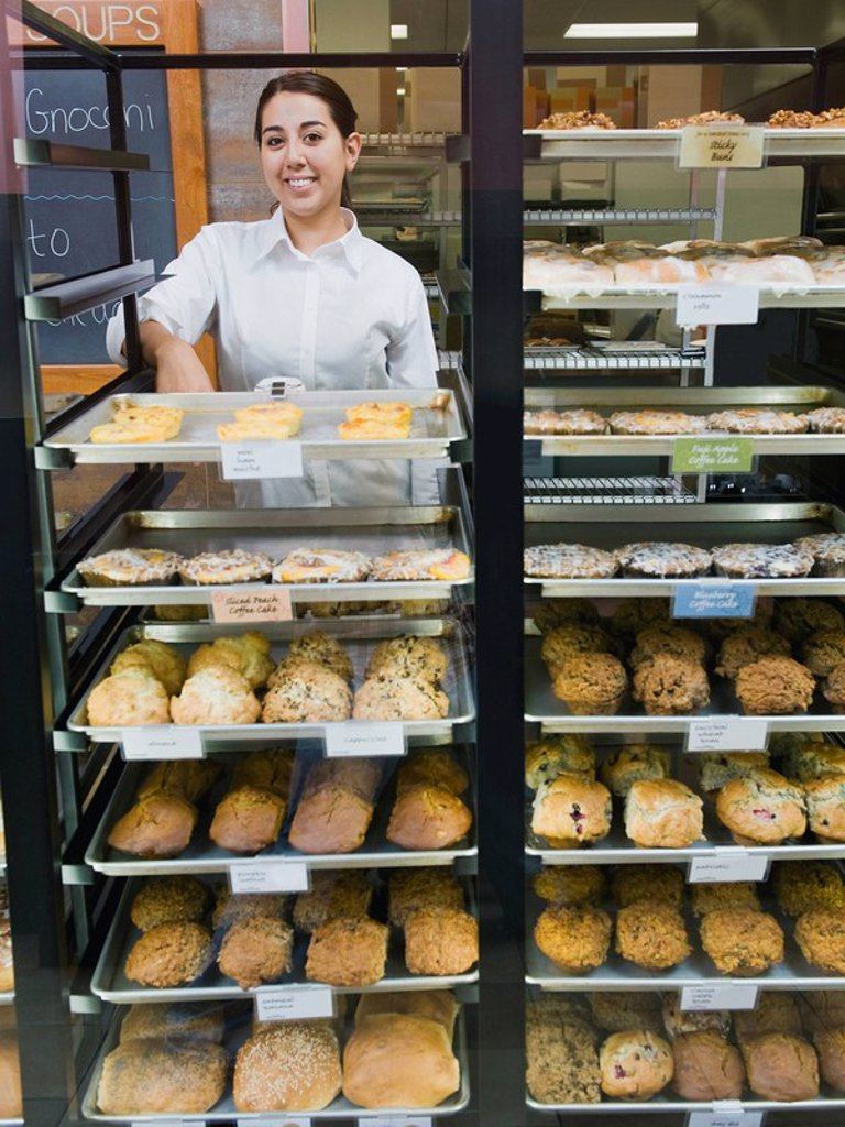 Baker standing behind trays of baked goods : Stock Photo