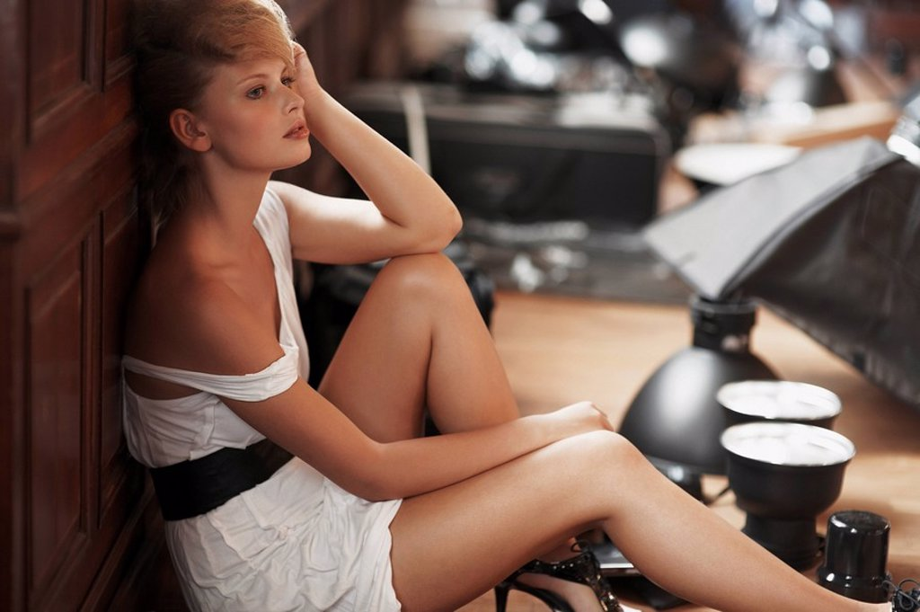 Bored fashion model sitting on floor : Stock Photo