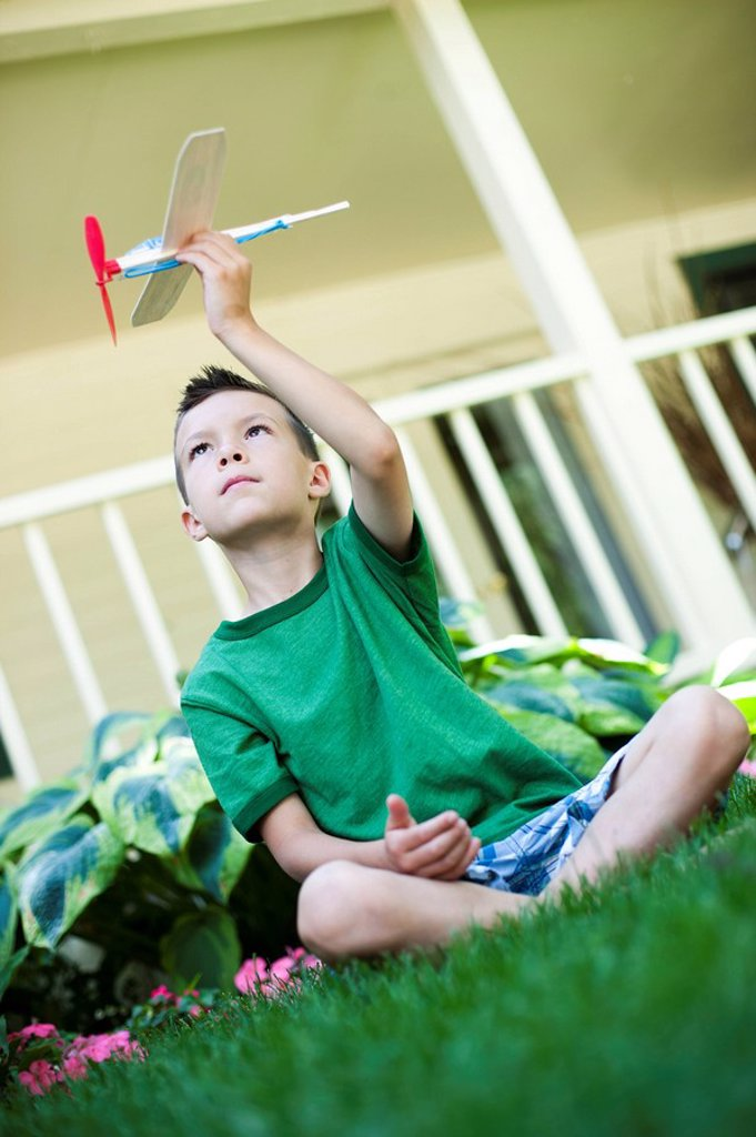 Stock Photo: 1795R-33147 Young boy playing with toy airplane