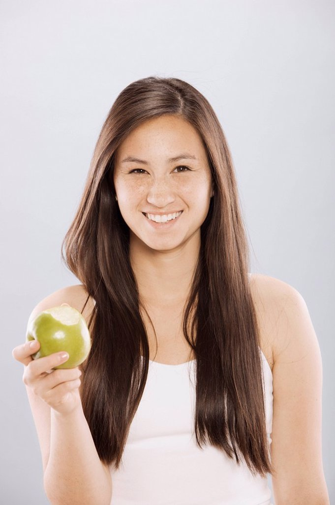 Stock Photo: 1795R-33190 Brunette woman holding an apple