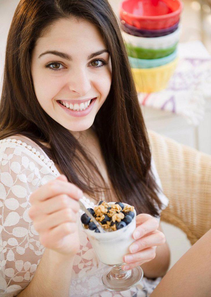 Brunette woman eating granola and yogurt : Stock Photo