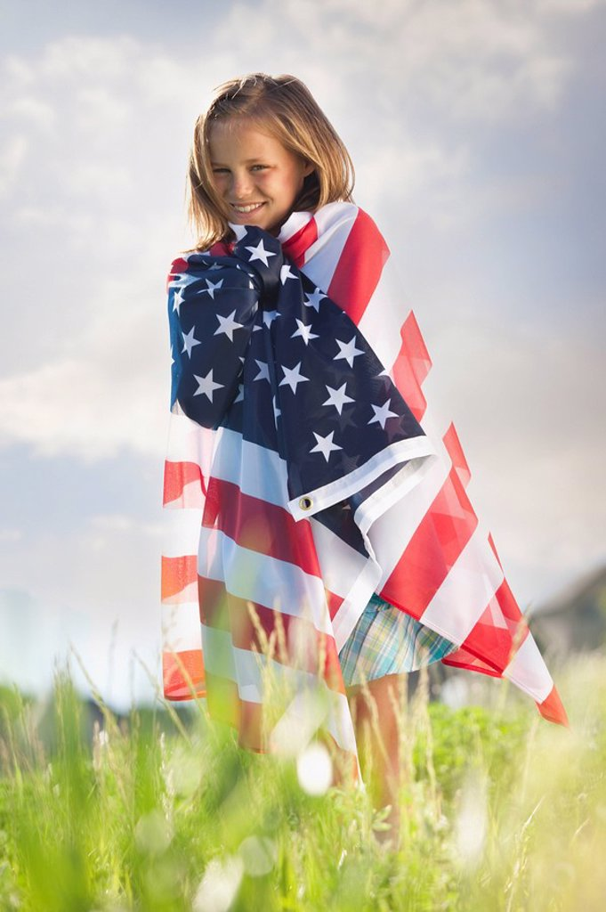 Young girl draped in American flag : Stock Photo