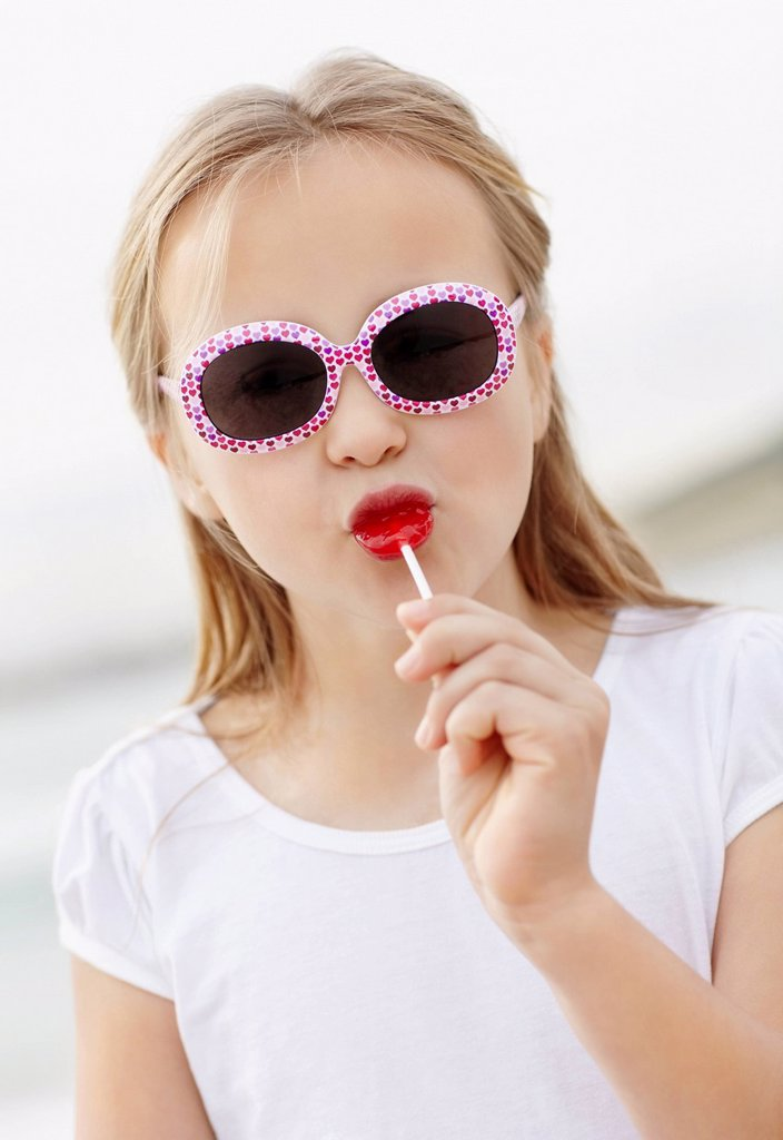 Girl 10_11 wearing sunglasses on beach is licking lollypop : Stock Photo