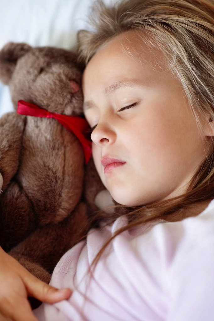 Stock Photo: 1795R-33812 Sad girl 10_11 sleeping in bed with teddybear