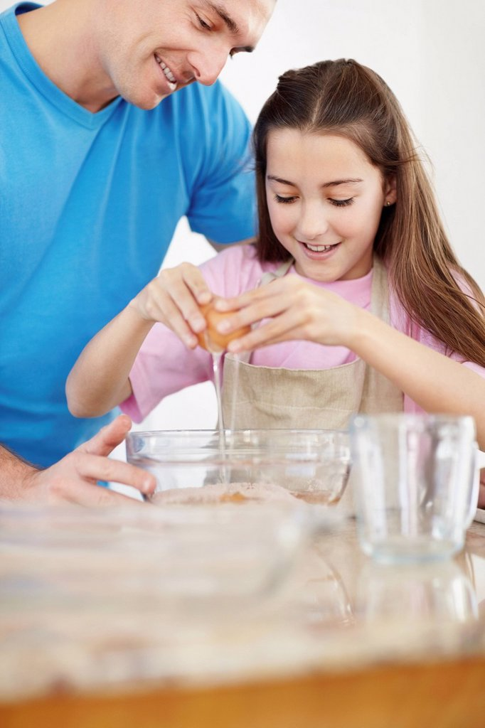 Daughter 10_11 helping father prepare food : Stock Photo