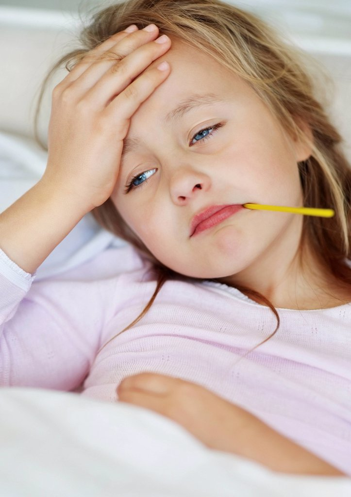 Sad girl 10_11 lying in bed with thermometer in mouth : Stock Photo