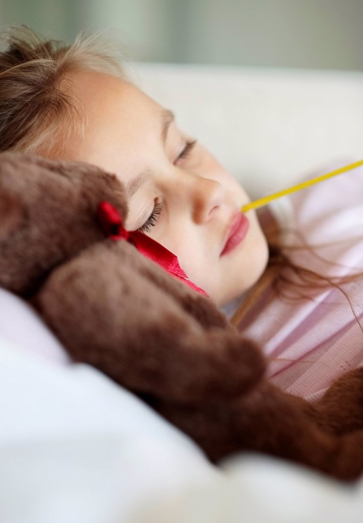 Stock Photo: 1795R-34892 Sad girl 10_11 lying in bed with teddybear and thermometer in mouth