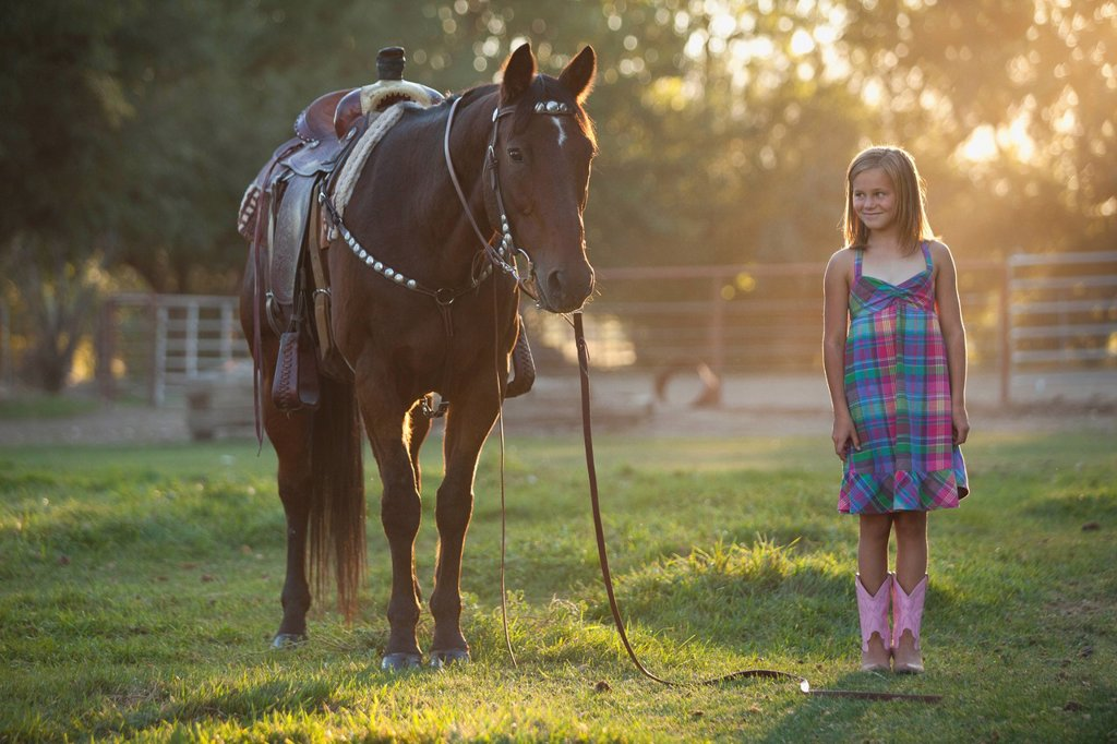 Girl 8_9 standing with horse in paddock : Stock Photo