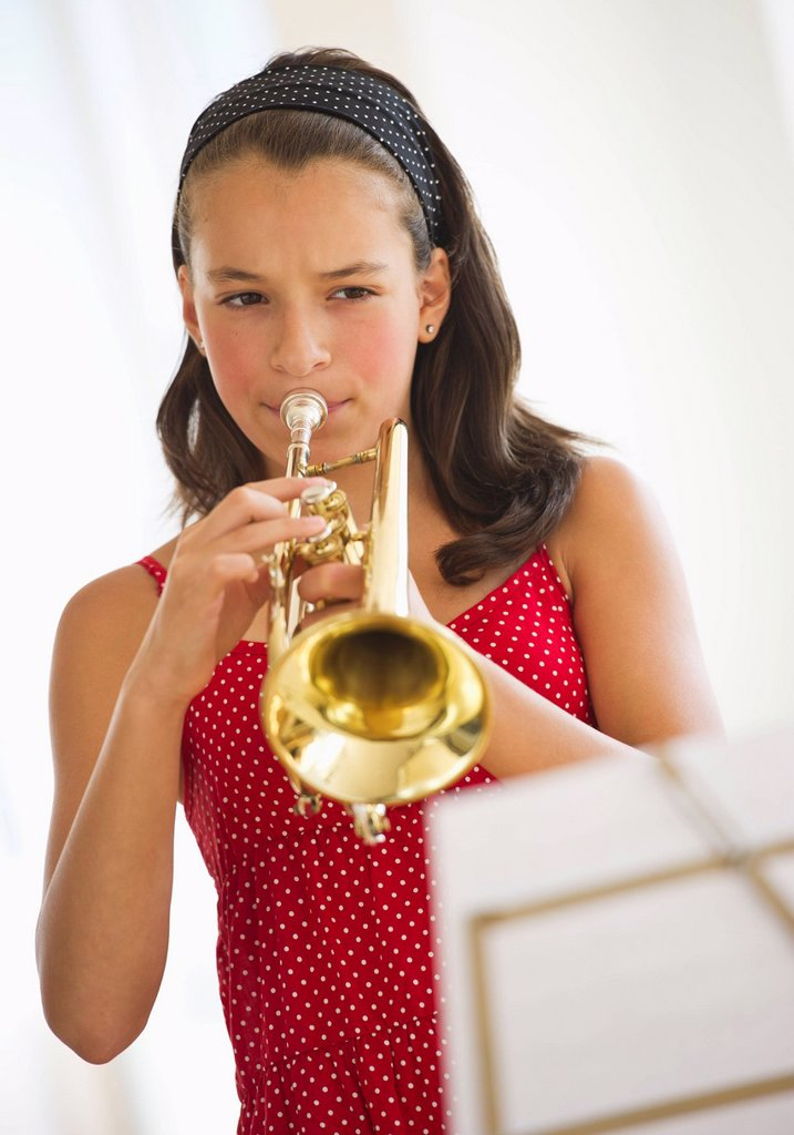 Girl 12_13 playing trumpet : Stock Photo