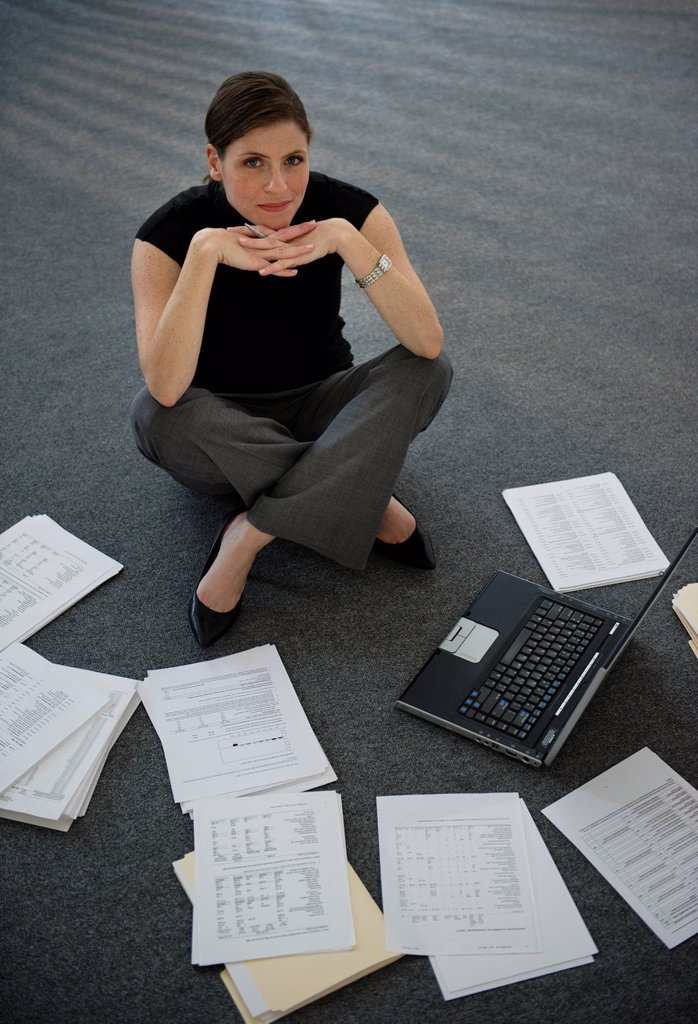 Woman sitting on floor with laptop with documents around : Stock Photo