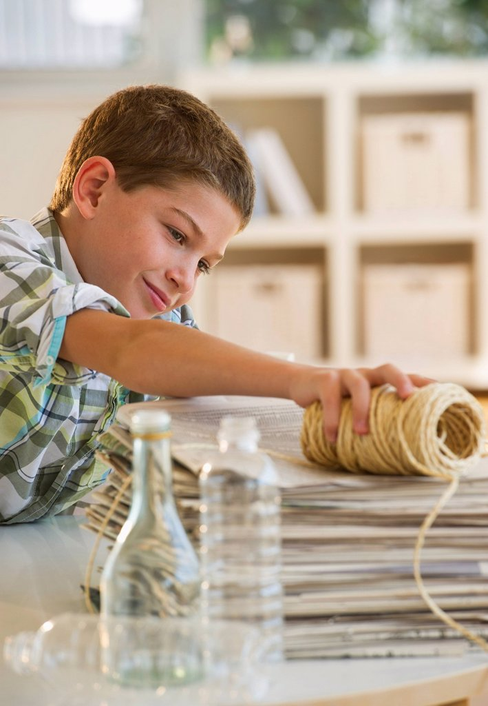 Boy 10_11 sorting garbage at home : Stock Photo
