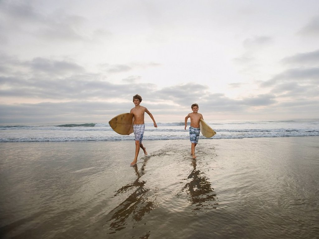 Boys running with surfboards : Stock Photo