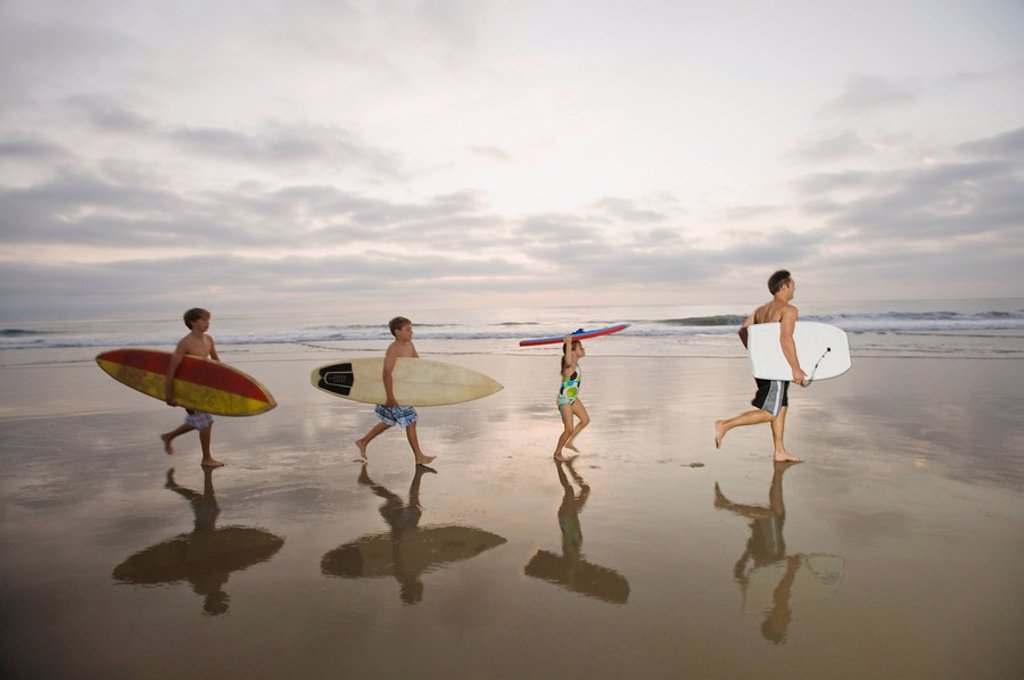 Family carrying surfboards : Stock Photo