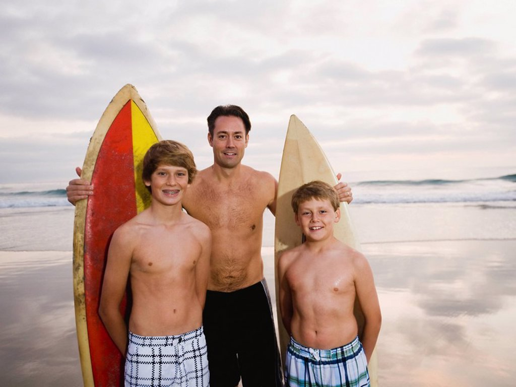 Father and sons standing with surfboards : Stock Photo
