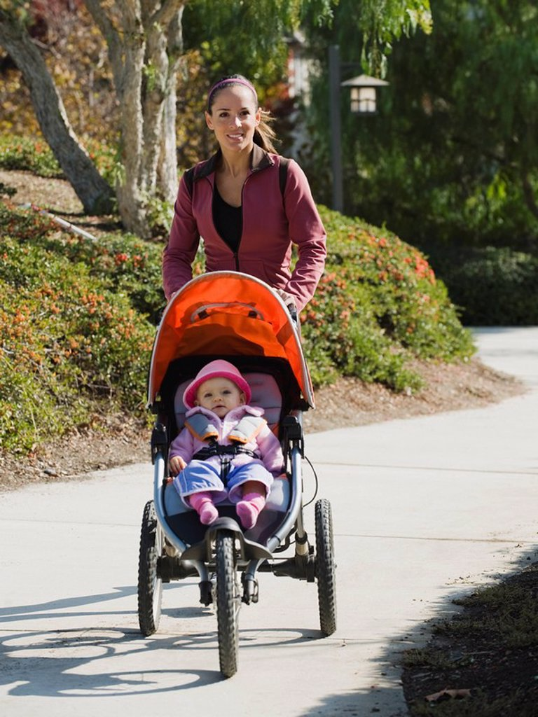 Woman jogging with stroller : Stock Photo