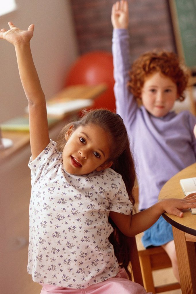 Girls raising hands in classroom : Stock Photo
