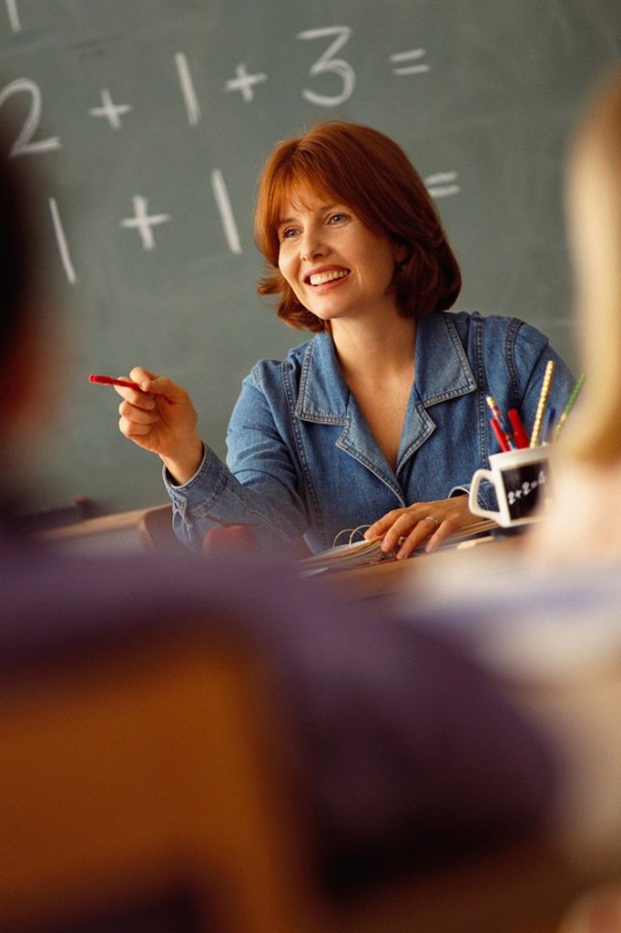 Stock Photo: 1795R-38284 Teacher sitting at desk in classroom