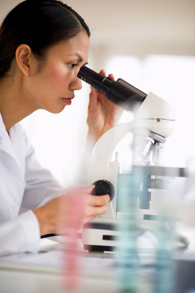 Stock Photo: 1795R-39189 USA, New Jersey, Jersey City, Female scientist using microscope behind test tubes