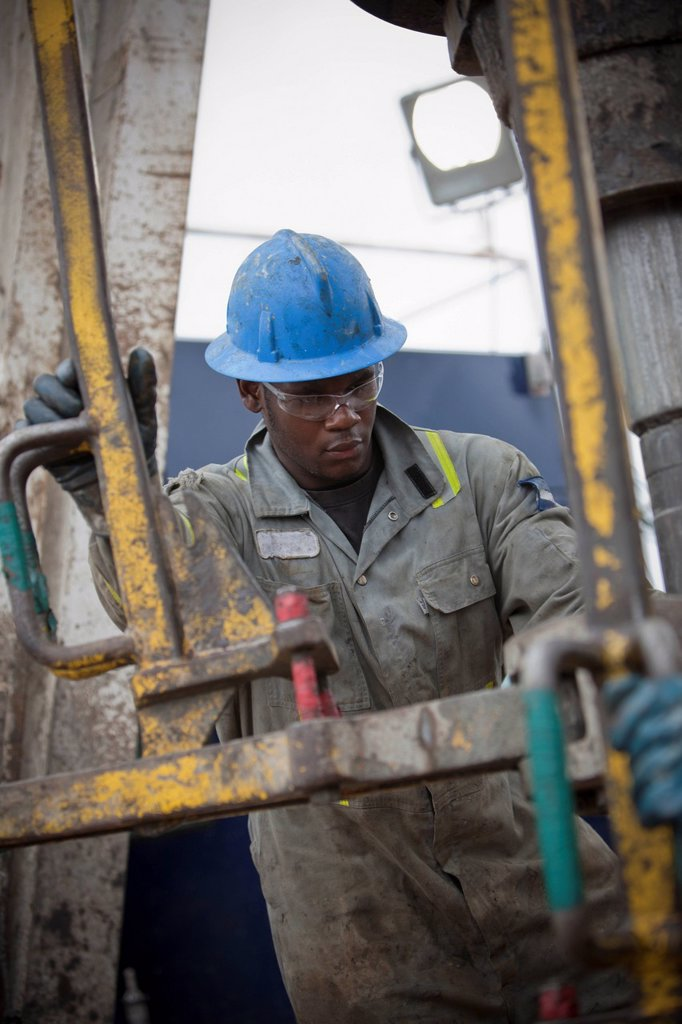 Oil worker drilling for oil on rig : Stock Photo