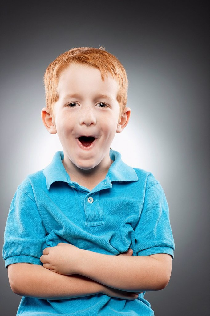 Portrait of smiling redhead boy 4_5 wearing blue polo shirt and making face, studio shot : Stock Photo
