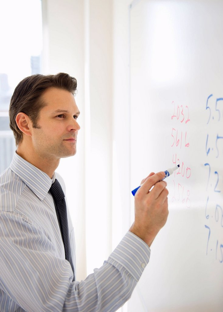 Businessman writing on whiteboard : Stock Photo