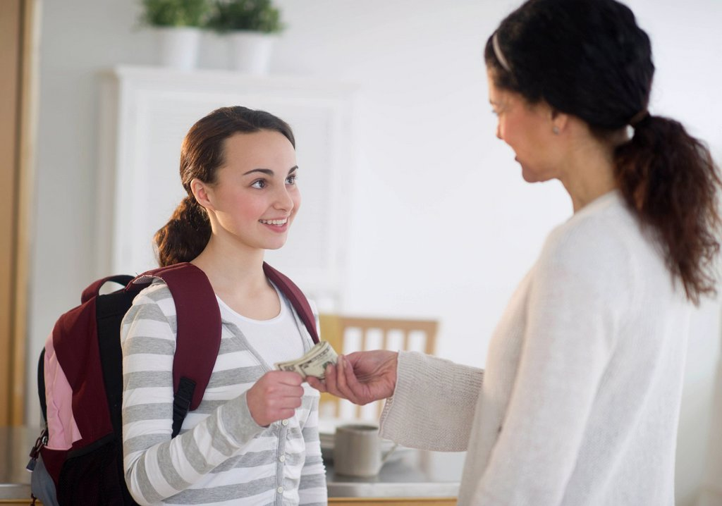 Mother giving money to teenage daughter 14_15 : Stock Photo