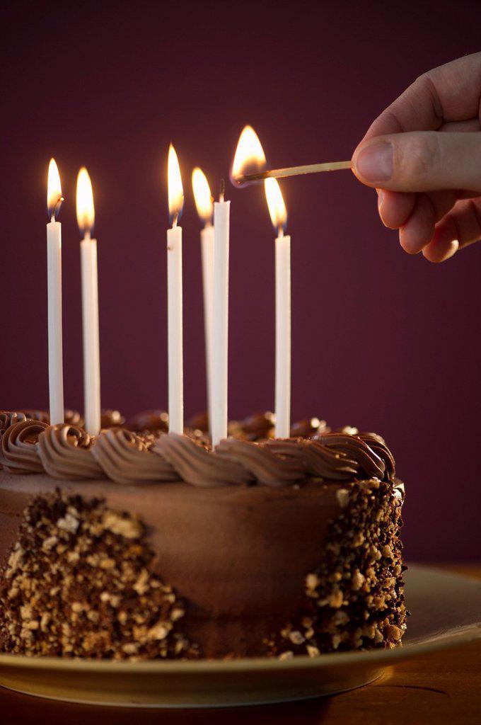 Stock Photo: 1795R-41332 Studio shot of man igniting candles on chocolate birthday cake