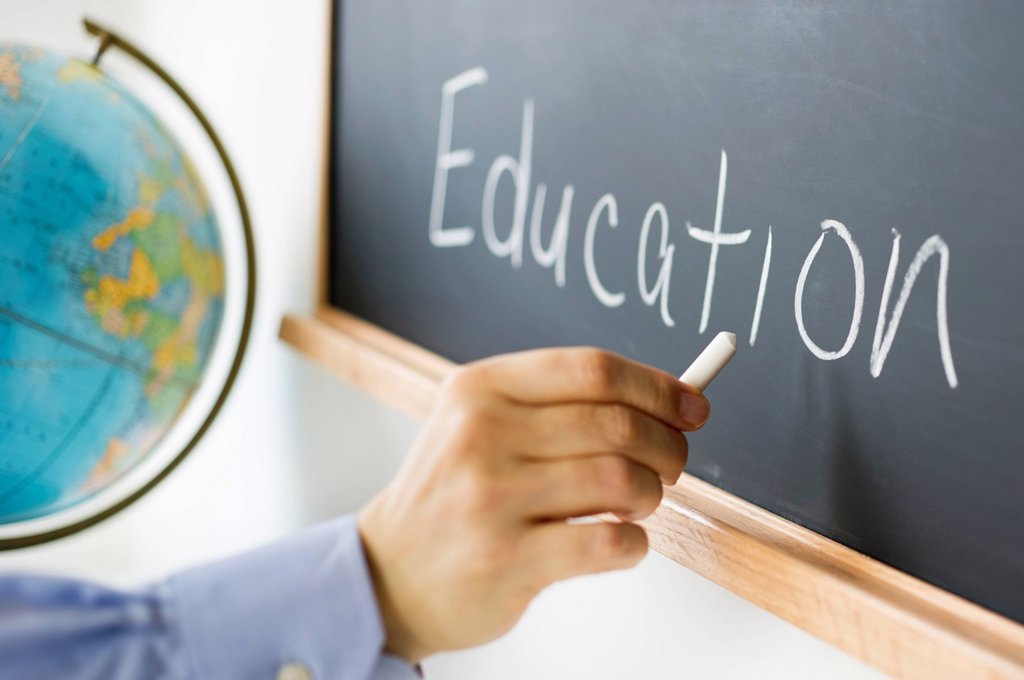 Close_up of man´s hand writing education on blackboard : Stock Photo