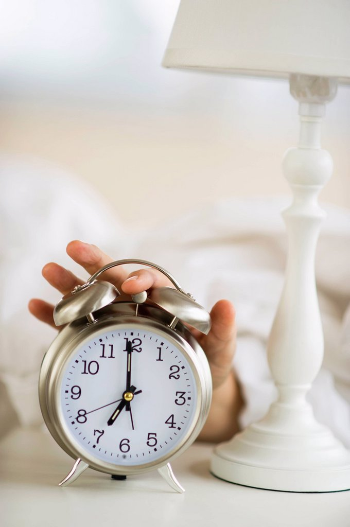 Close_up of man´s hand reaching to alarm clock from bed : Stock Photo