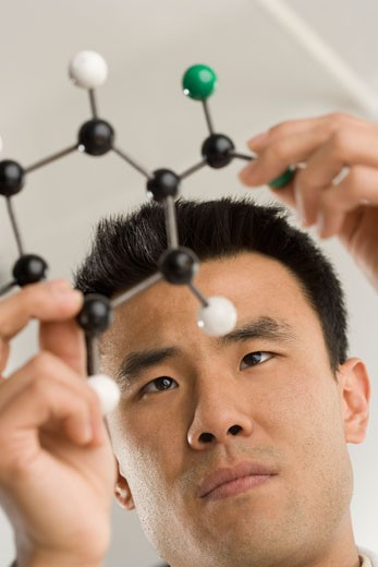 Stock Photo: 1795R-4137 Scientist examining molecular structure