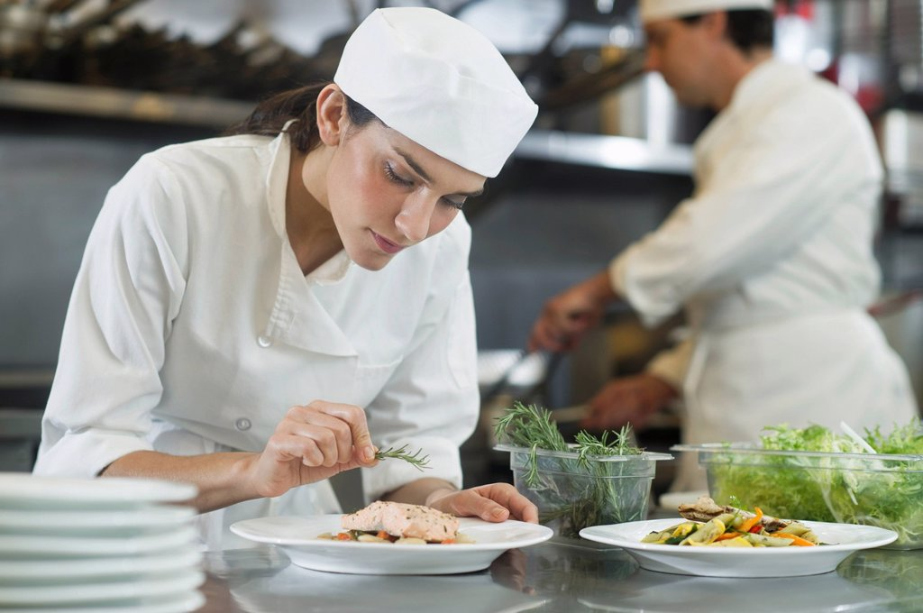 Chef and cook preparing food in commercial kitchen : Stock Photo