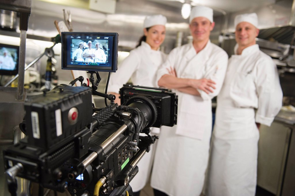 Three chefs posing in kitchen, camera in foreground : Stock Photo