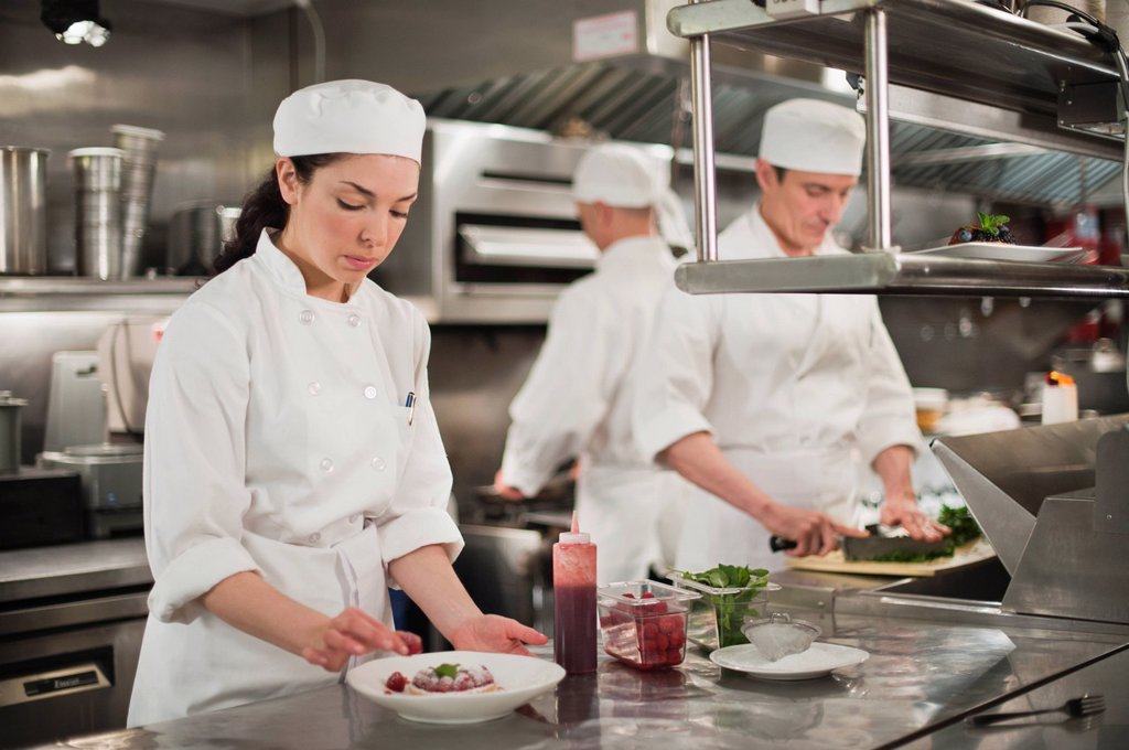 Chefs preparing food in kitchen : Stock Photo