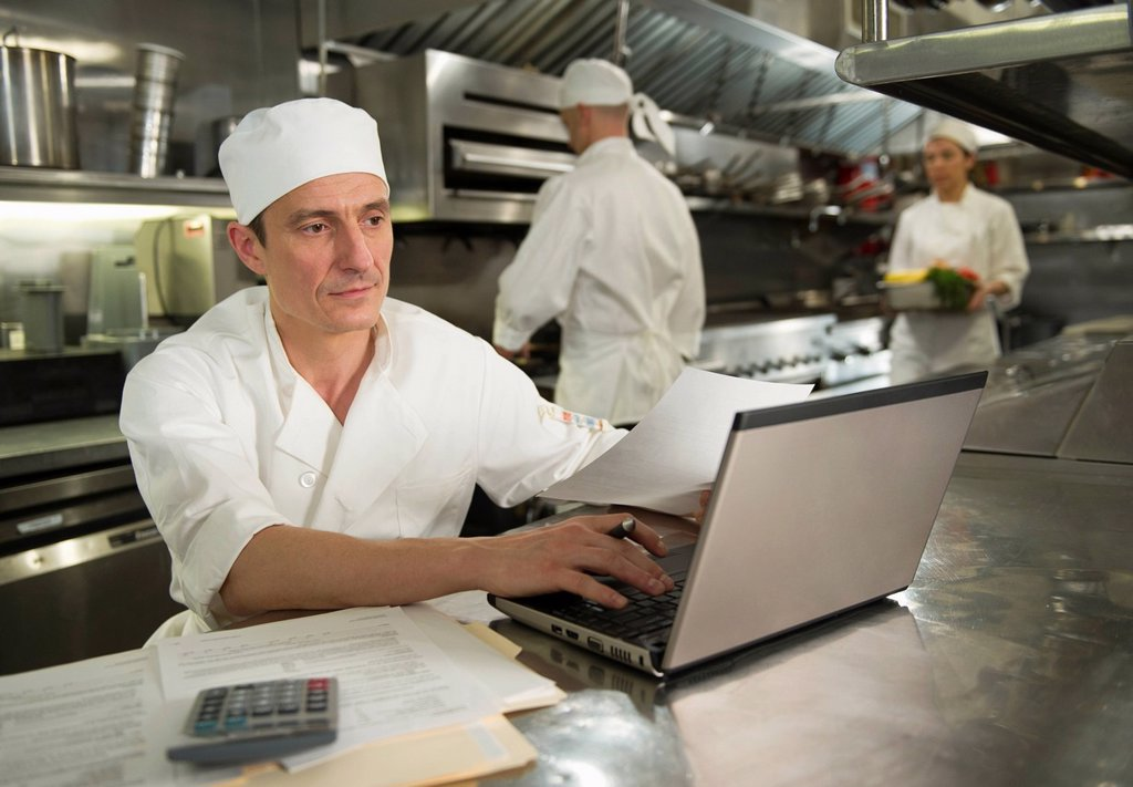Chefs preparing food, one working on laptop : Stock Photo