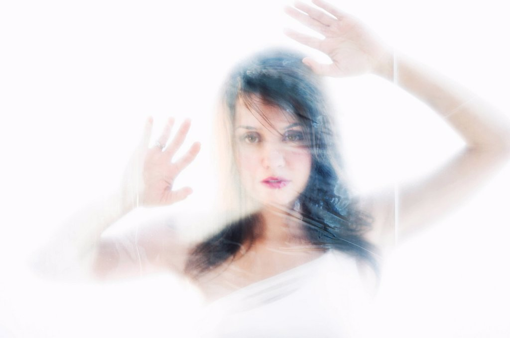 Young attractive woman looking from behind white sheet : Stock Photo