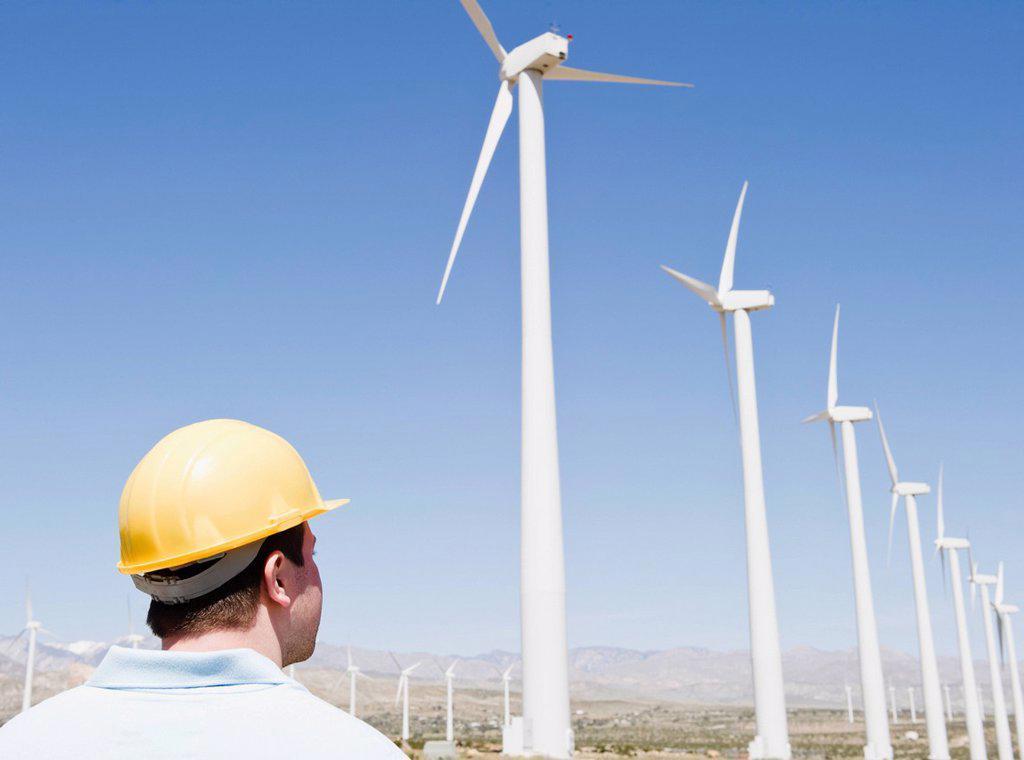 USA, California, Palm Springs, Coachella Valley, San Gorgonio Pass, Man in hard hat looking at wind turbines : Stock Photo