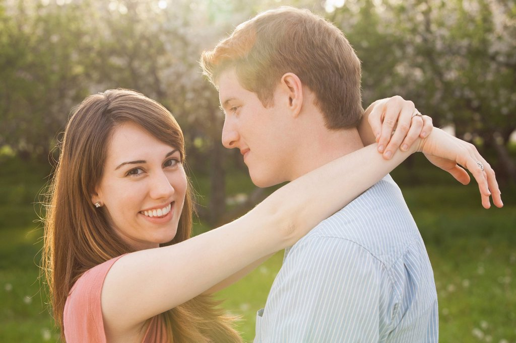 Young couple embracing in orchard : Stock Photo
