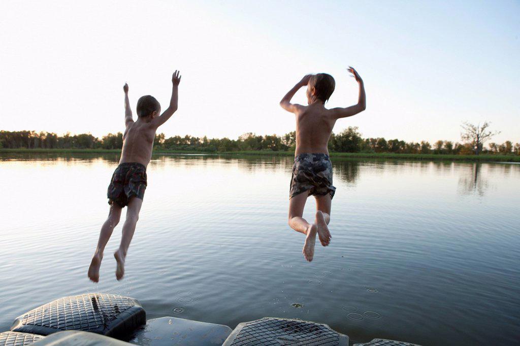 USA, Texas, Texarkana, Two boys 8_9 jumping into lake : Stock Photo