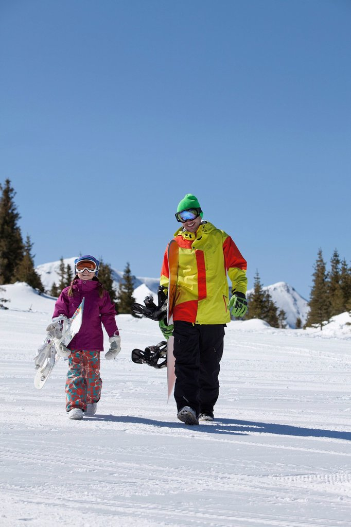 Stock Photo: 1795R-42544 USA, Colorado, Telluride, Father and daughter 10_11 walking with snowboards in winter scenery