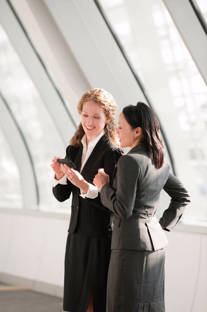 USA, Virginia, Virginia Beach, businesswomen looking at cell phone : Stock Photo