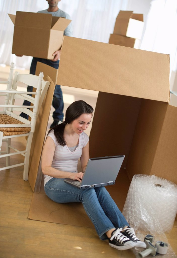 Woman using laptop by cardboard box : Stock Photo