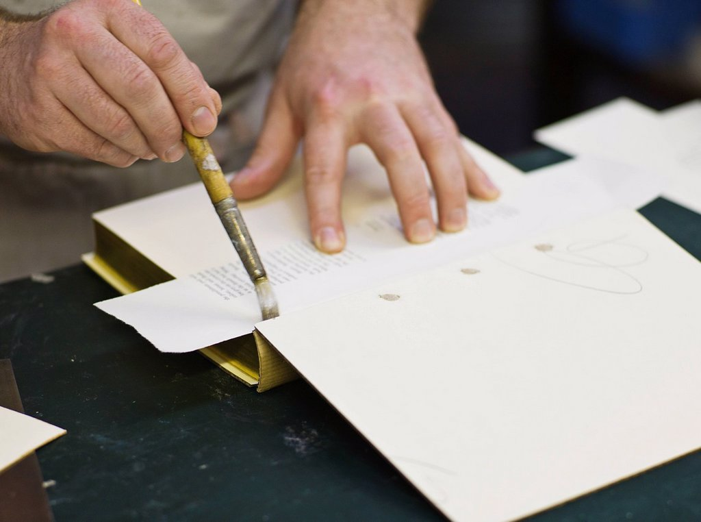 Craftsman making book bindings : Stock Photo
