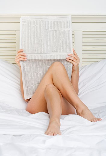 Woman in bed reading business section : Stock Photo