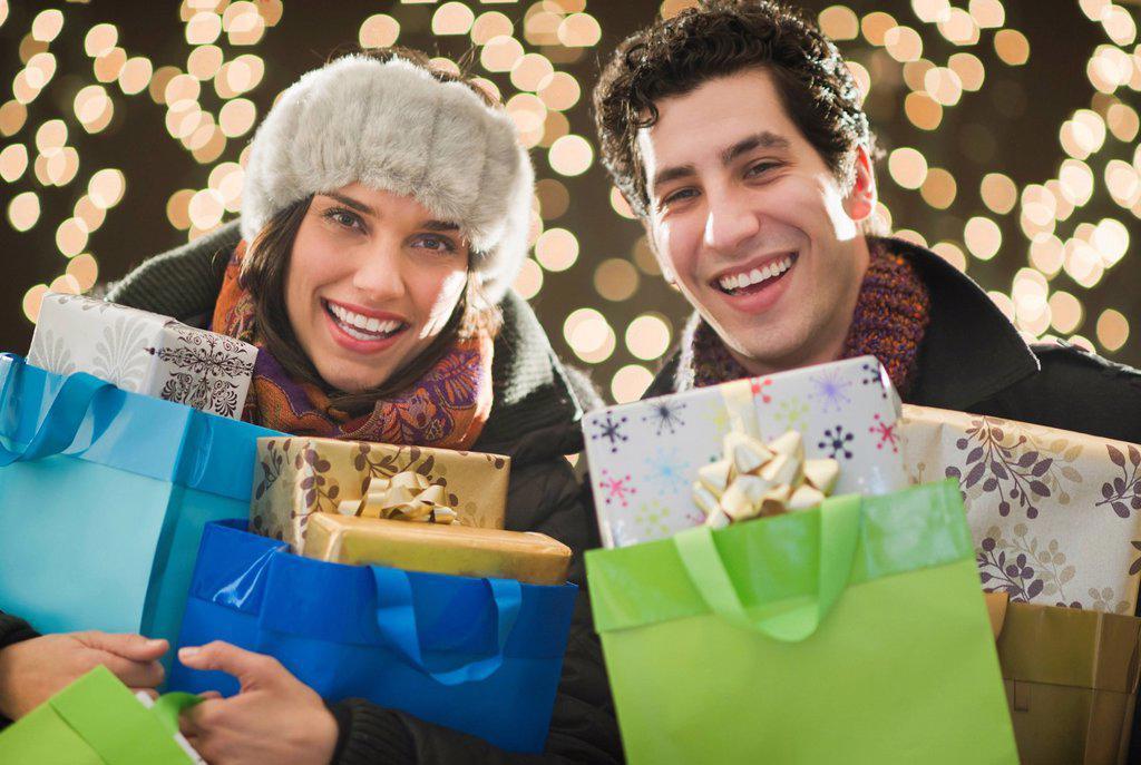 Happy couple holding Christmas presents : Stock Photo